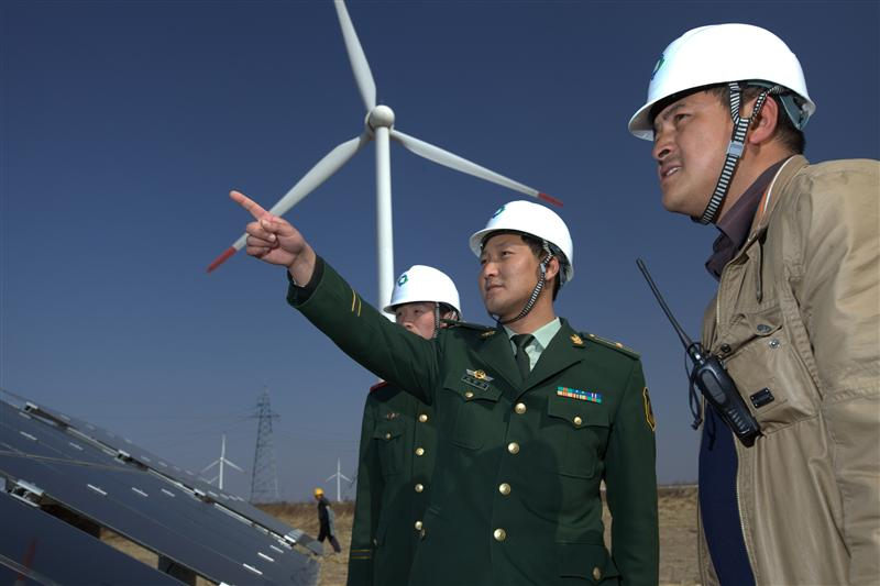 Workers at Dafeng Power Station, Chinas largest solar photovoltaic-wind hybrid power station, with 220MW of grid-connected capacity, of which 20 MW is solar PV. Located in Yancheng, Jiangsu province, it came into operation on December 31, 2010 and has 1,100 annual utilization hours.   Every year it can generate 23 million KW-h of electricity, allowing it to save 7,000 tons of coal and 18,600 tons of carbon dioxide emissions.